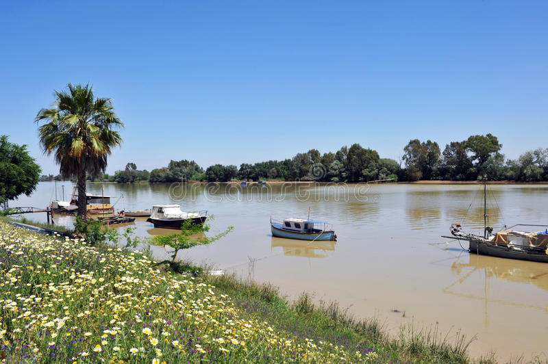 Small boats at the pier on the Guadalquivir River as it passes through Coria del Rio, Seville province, Andalusia, Spain. Fishing boats and barges on the River stock photography