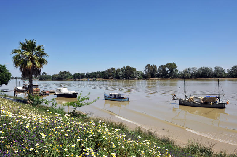 Small boats at the pier, the Guadalquivir River as it passes through Coria del Rio, Seville province, Andalusia, Spain. Fishing boats and barges on the River stock image
