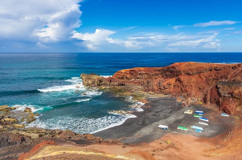 Small boats on a volcanic sand beach stock photo