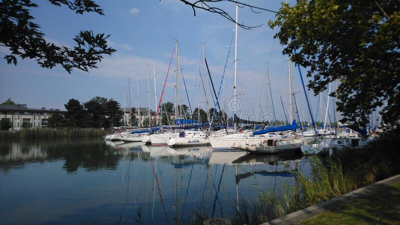 Small boats and yachts in a small port at Lake Balaton, Hungary. Summer picture, mostly white but colorful small boats and yachts waiting for their owners in the royalty free stock photo