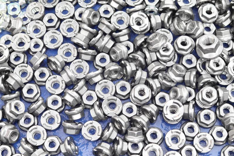 Small bolts and nuts by manufacturing process. Tapping, steel, background, screw, metal, chrome, thread, mechanic, scattered, work, equipment, construction royalty free stock photography