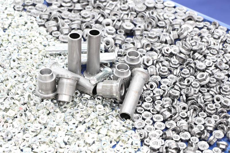 Small bolts and nuts by manufacturing process. Tapping, steel, background, screw, metal, chrome, thread, mechanic, scattered, work, equipment, construction royalty free stock photo