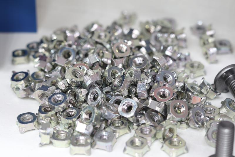 Small bolts and nuts by manufacturing process. Tapping, steel, background, screw, metal, chrome, thread, mechanic, scattered, work, equipment, construction stock images