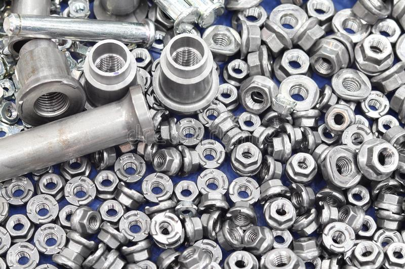 Small bolts and nuts by manufacturing process. Tapping steel background screw metal chrome thread mechanic scattered work equipment construction industry royalty free stock photo