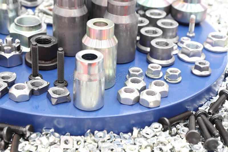 Small bolts and nuts by manufacturing process. Tapping, steel, background, screw, metal, chrome, thread, mechanic, scattered, work, equipment, construction royalty free stock image