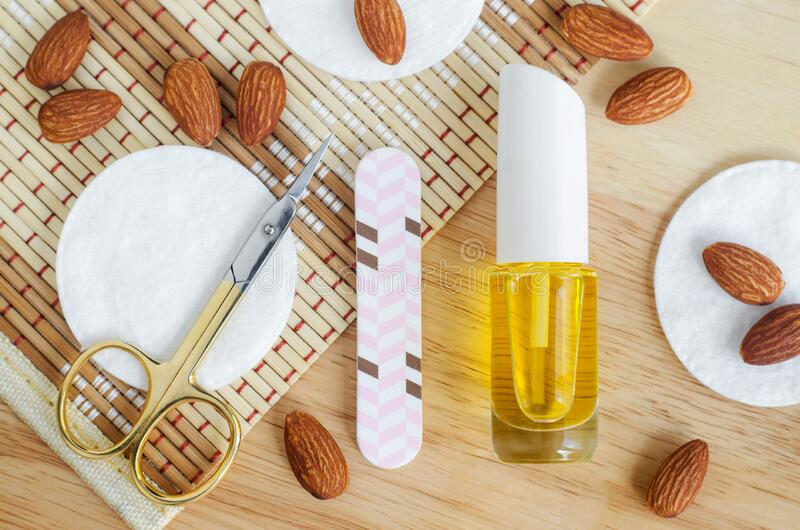 Small bottle with almond oil, scissors and nail file for natural nails and cuticle treatment. Homemade manicure and pedicure. Concept. Top view, copy space stock photography