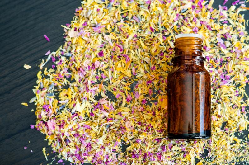 Small bottle with essential oil and dry herbs and flowers. Background with colorful dried flowers petals. Aromatherapy and spa royalty free stock images