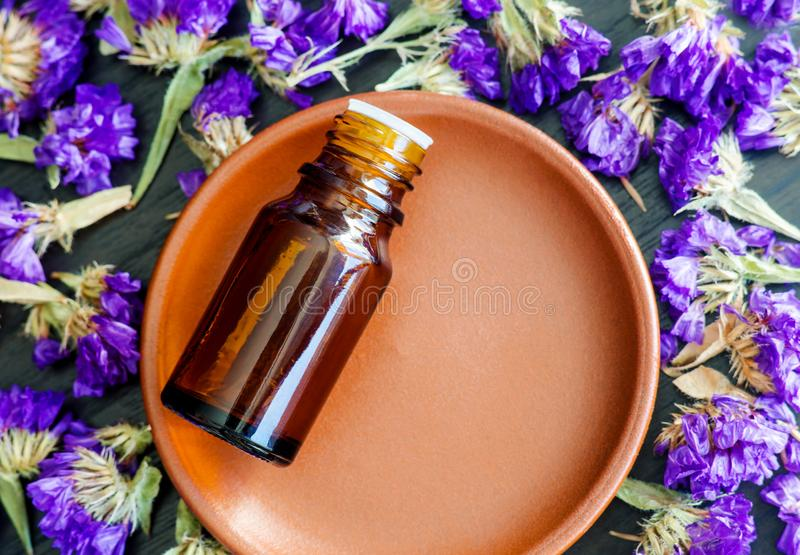 Small bottle with essential oil on the small ceramic plate. Dark wooden background with dry purple flowers. Aromatherapy and spa royalty free stock photos