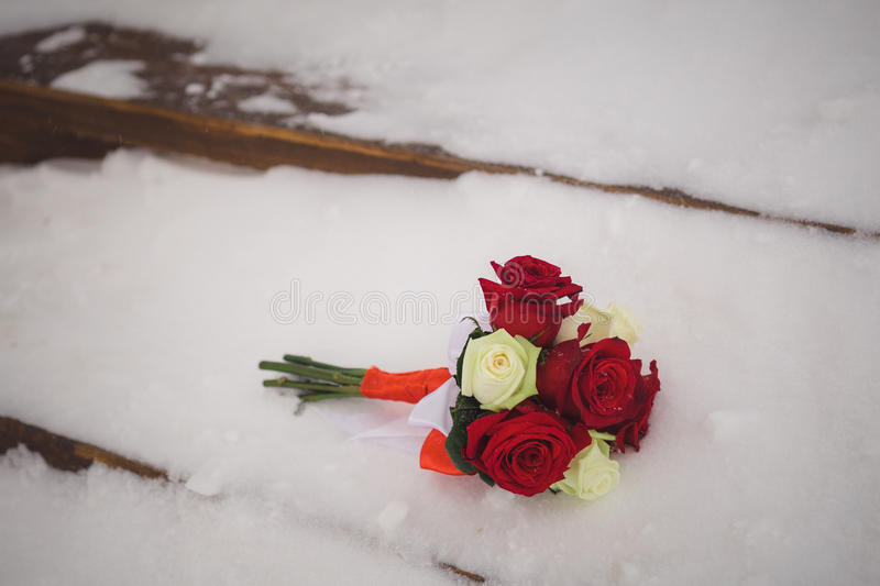 A small bouquet of the bride lies on the snow-covered steps, wedding stock photo