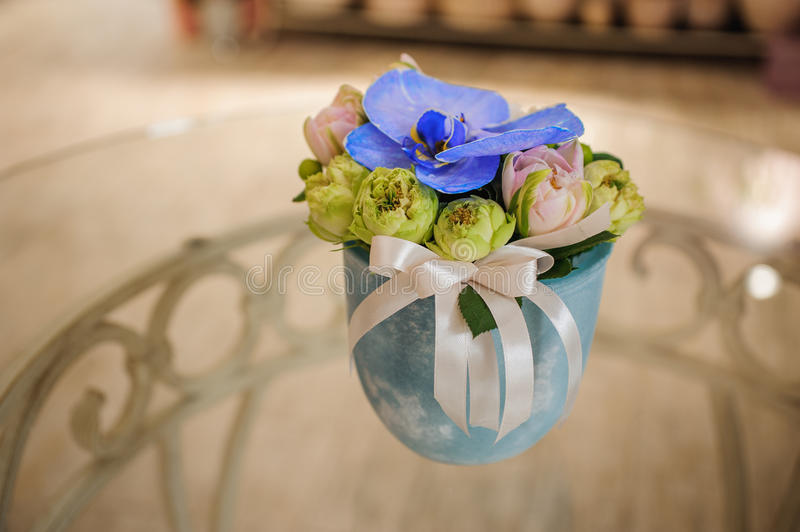 Small bouquet of flowers with blue orchid. In vase royalty free stock photo