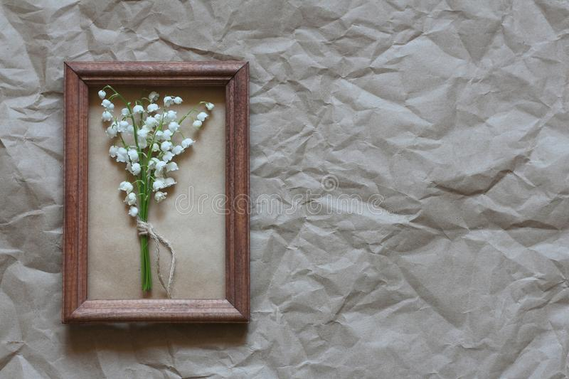 Small bouquet of lilies of the valley in a wooden frame on the crumpled Kraft paper background royalty free stock photo