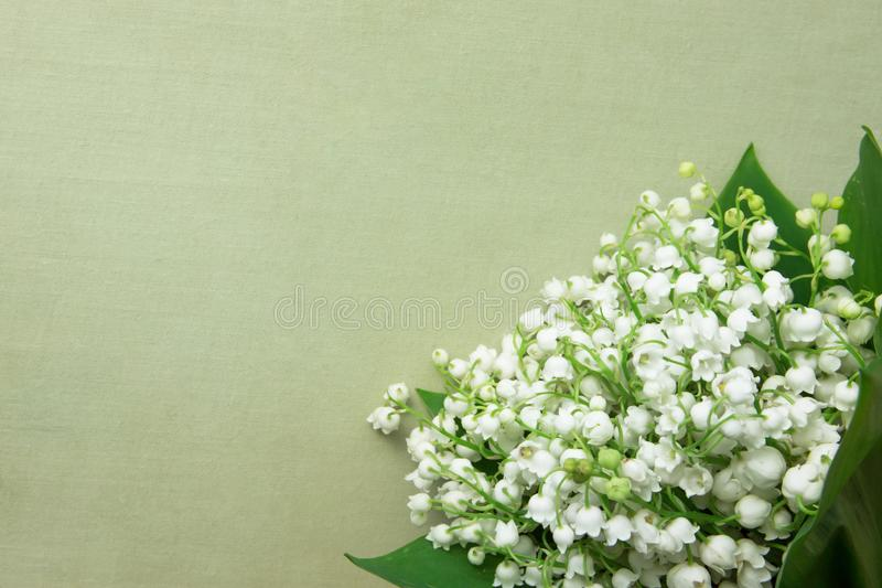 Small Bouquet of Lily of the Valley Flowers with Green Leaves on Beige Vintage Background. Wedding Birthday Mother`s Women`s Day royalty free stock photos