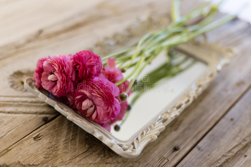 Small bouquet of pink ranunculus lying on vintage tray royalty free stock images