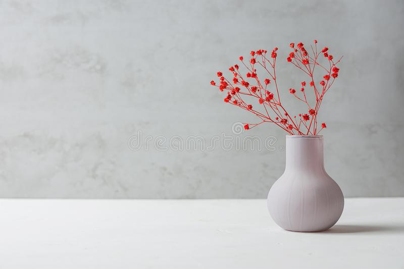 Small Bouquet of Red Flowers in Vintage Vase on White Table Grey Cement Wall Background. Styled Stock Image Mockup for Text Art royalty free stock photo