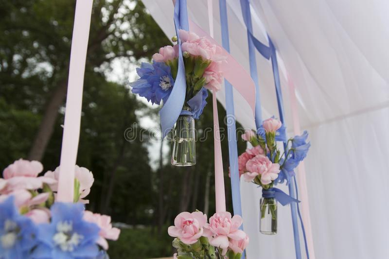 Small bouquets of flowers in glass vases hang on satin ribbons stock photography