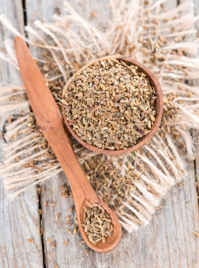 Small bowl with Aniseed. (Pimpinella Anisum) on wooden background stock photo