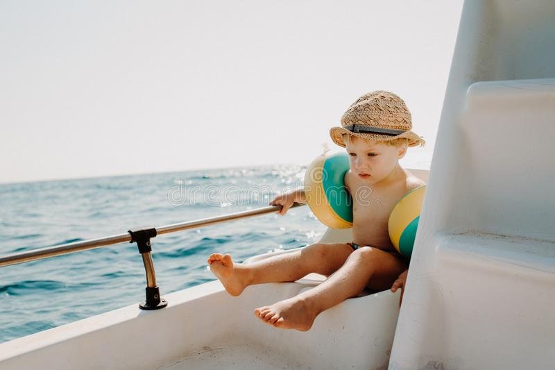 A small boy with armbands sitting on boat on summer holiday. stock photo