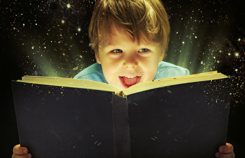 Small boy carrying a magic book. Small boy carrying an old magic book royalty free stock photography