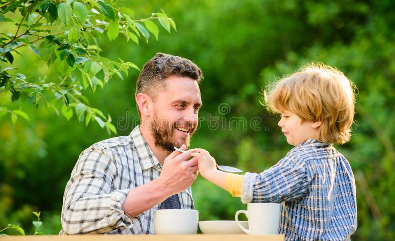Small boy child with dad. father and son eat outdoor. they love eating together. Weekend breakfast. healthy food. Family. Day bonding. organic and natural food royalty free stock photography
