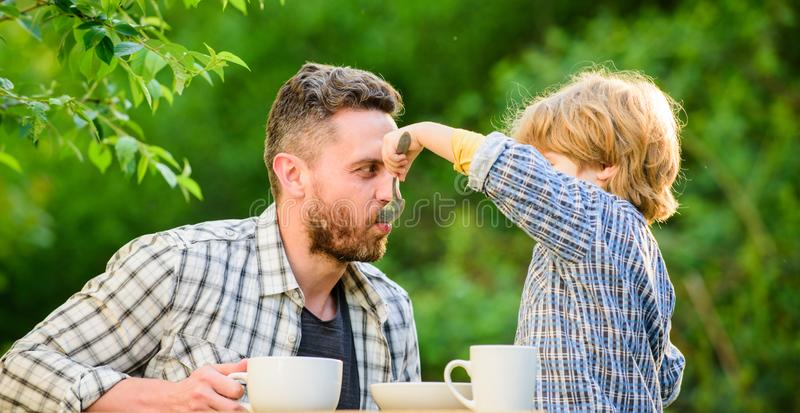 Small boy child with dad. they love eating together. Weekend breakfast. father and son eat outdoor. organic and natural. Food. healthy food. Family day bonding royalty free stock image
