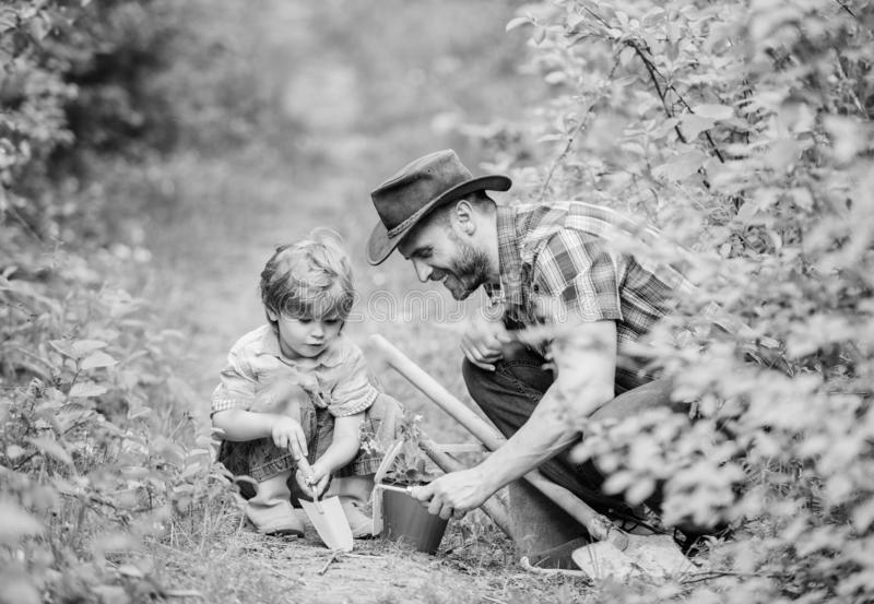 Small boy child help father in farming. Eco farm. father and son in cowboy hat on ranch. hoe, pot and shovel. Garden. Equipment. happy earth day. Family tree royalty free stock photography