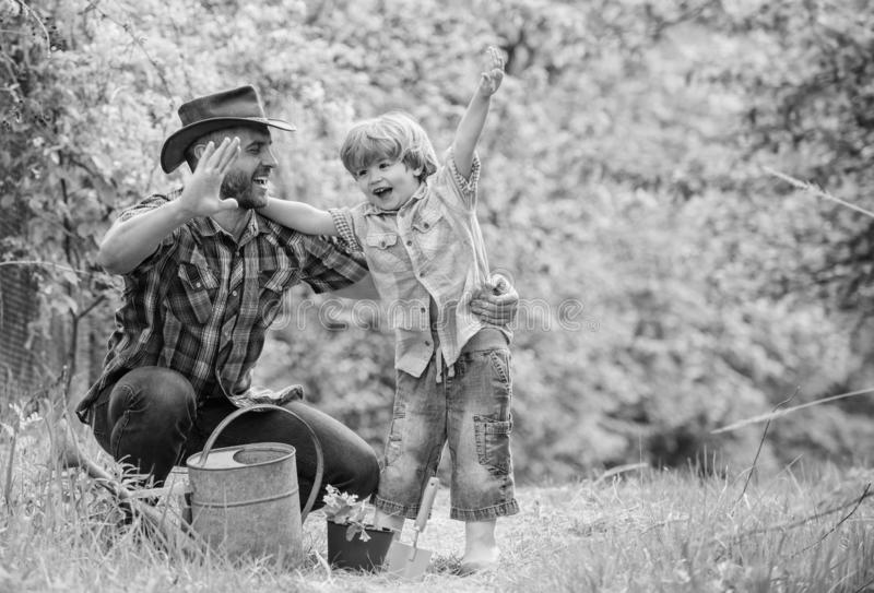 Small boy child help father in farming. happy earth day. Family tree nursering. Eco farm. watering can, pot and hoe. Garden equipment. father and son in cowboy royalty free stock image