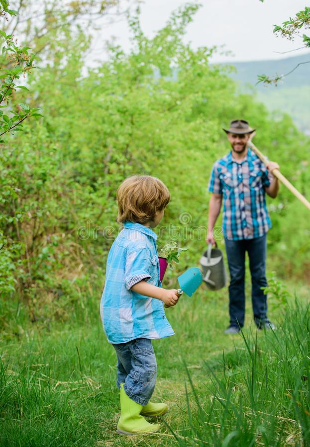Small boy child help father in farming. happy earth day. Family tree nursering. watering can, pot and hoe. Garden. Equipment. Eco farm. father and son in cowboy stock photos