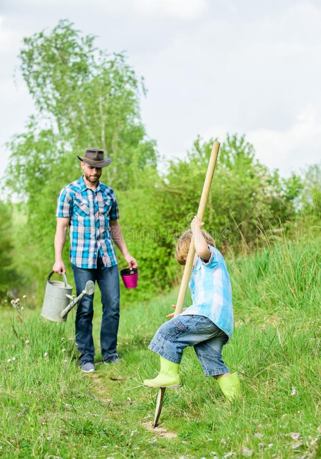 Small boy child help father in farming. new life. soils and fertilizers. father and son planting family tree. happy. Earth day. Dig grounf with shovel. rich stock images