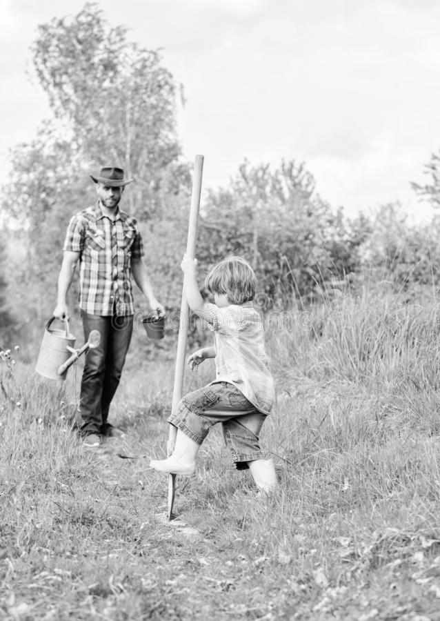 Small boy child help father in farming. new life. soils fertilizers. happy earth day. Dig grounf with shovel. father and. Son planting family tree. rich natural stock photos