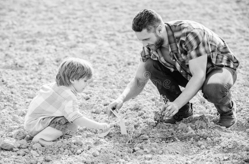 Small boy child help father in farming. rich natural soil. Eco farm. father and son planting flowers in ground. new life. Soils fertilizers. happy earth day stock images