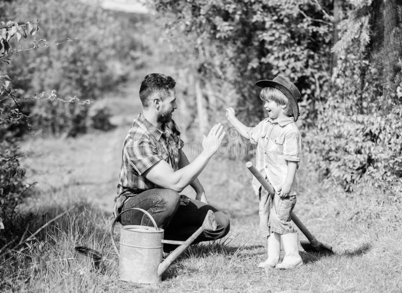 Small boy child help father in farming. use watering can and pot. Garden equipment. Eco farm. father son in cowboy hat royalty free stock photo