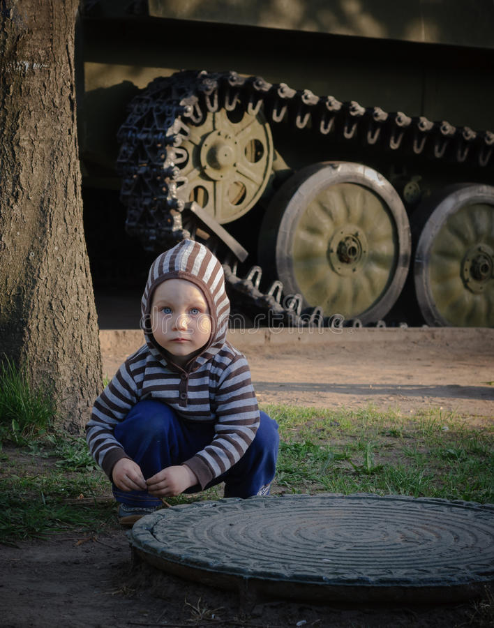 Small boy crouching beside tank royalty free stock images
