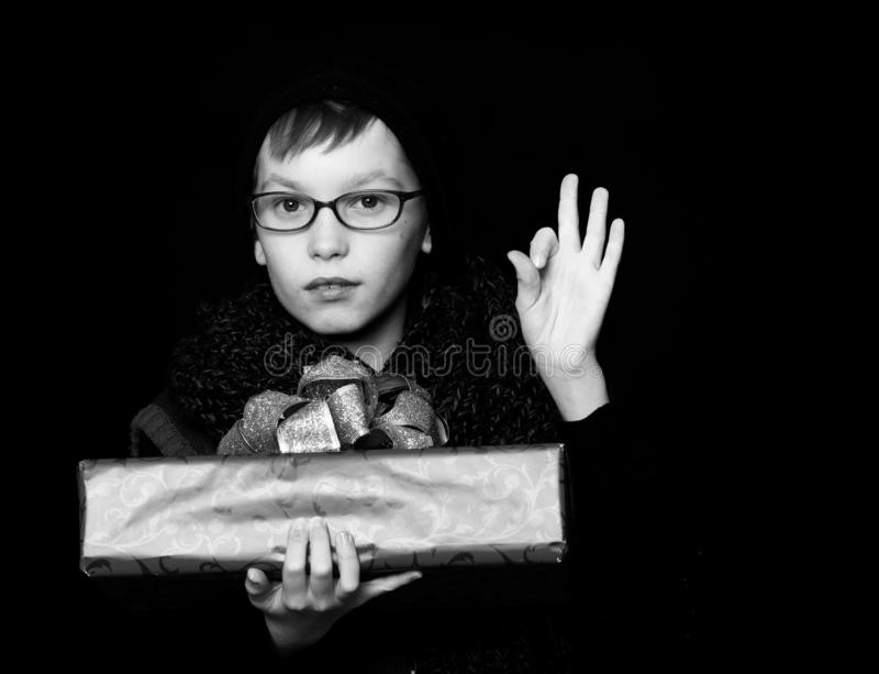 Small boy or cute nerd kid in glasses, hat and fashionable knitted scarf on black background holds red present box with. Golden bow and ok gesture stock photography