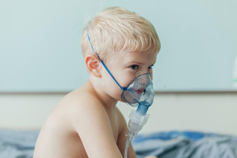 Small boy does therapeutic inhalation using a nebulizer. Indoor stock photo