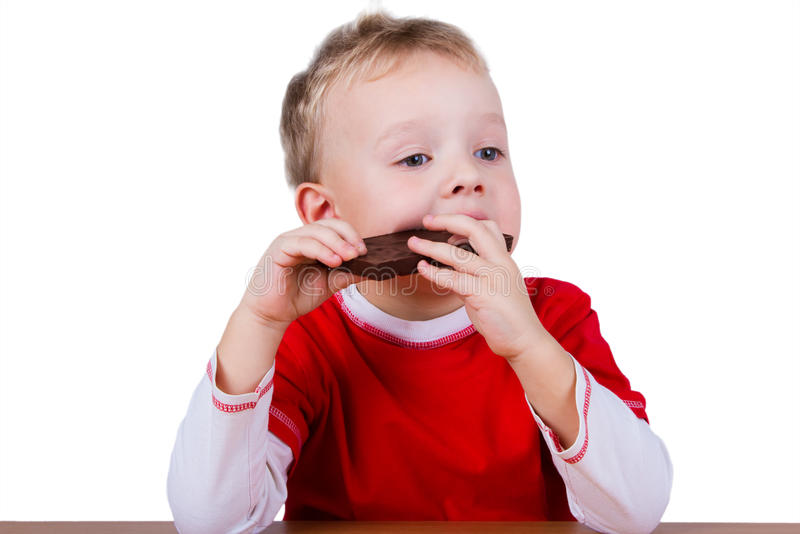 Small boy eating whole bar of chocolate stock images