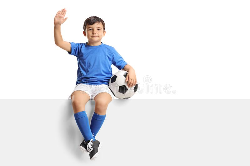 Small boy with a football sitting on a panel and waving stock photography