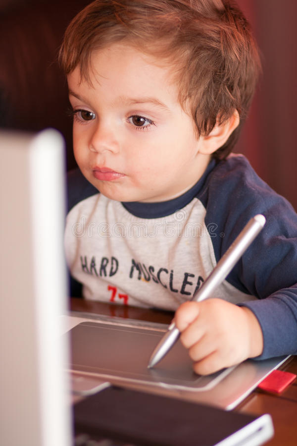 Small boy in front of a notebook stock images