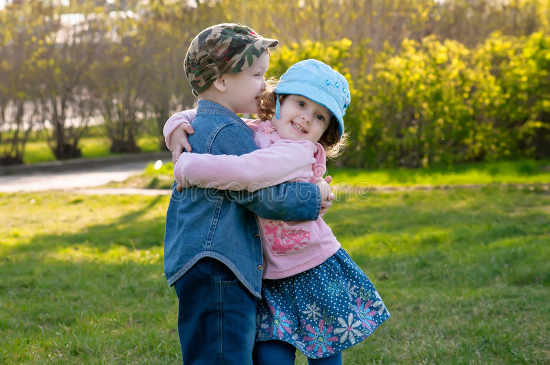 Small boy and the girl walk and embrace in park