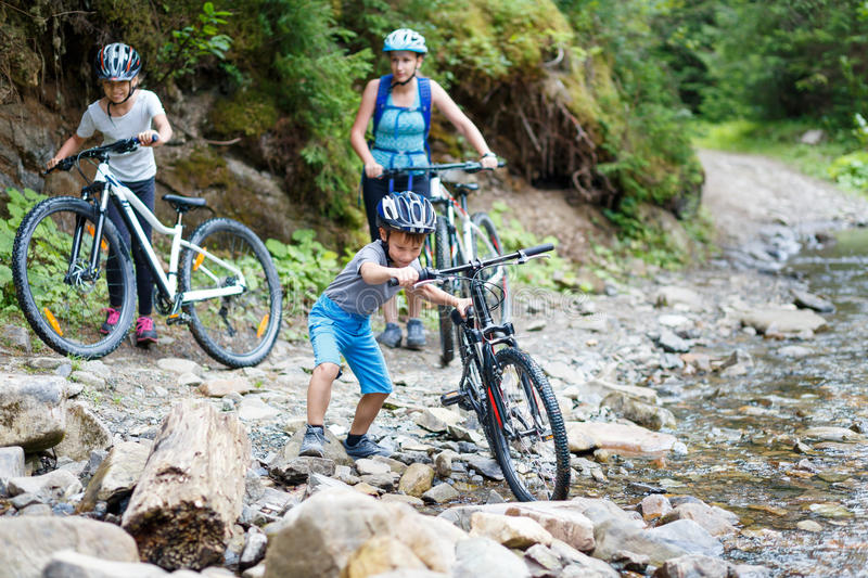 Small boy with his family on bikes wade the stream royalty free stock images