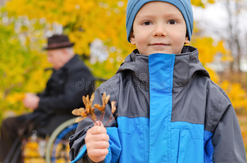 Small boy and his grandfather outdoors royalty free stock photo
