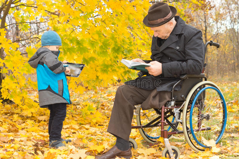 Small boy with his handicapped grandfather. Outdoors in a colourful fall garden with the old men sitting in his wheelchair reading while his grandson plays on a royalty free stock photo