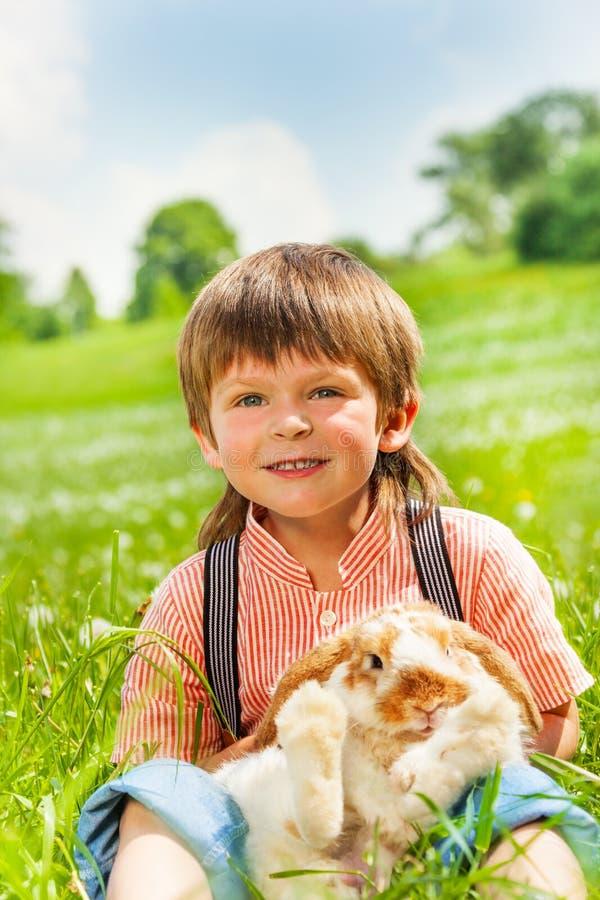 Small boy hugging rabbit in green field royalty free stock photos