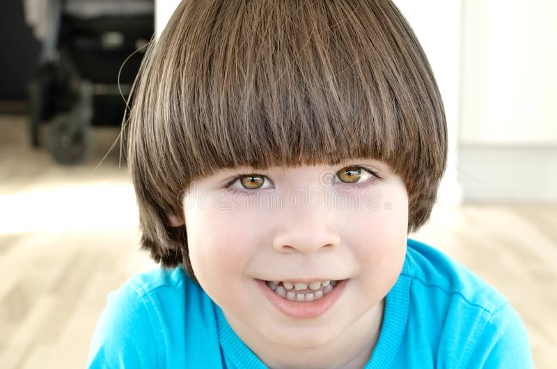 Small boy with long hair is smiling. And looking to the camera royalty free stock image