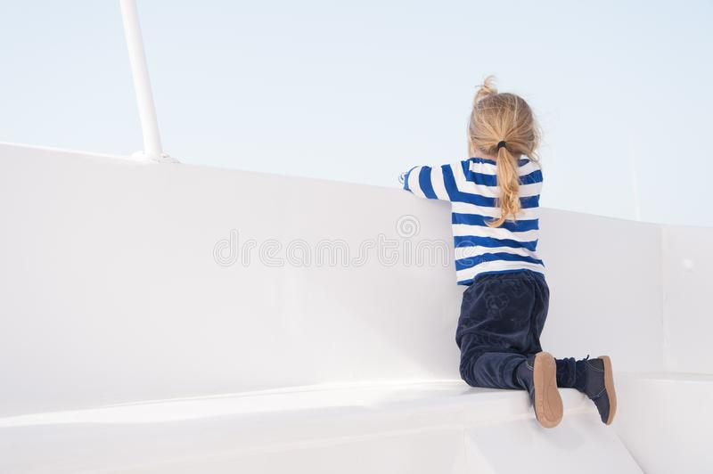 Small boy look from ship board, back view. Child on seat of boat on sunny blue sky. Kid with blond hair in navy clothes. Kids fash stock images