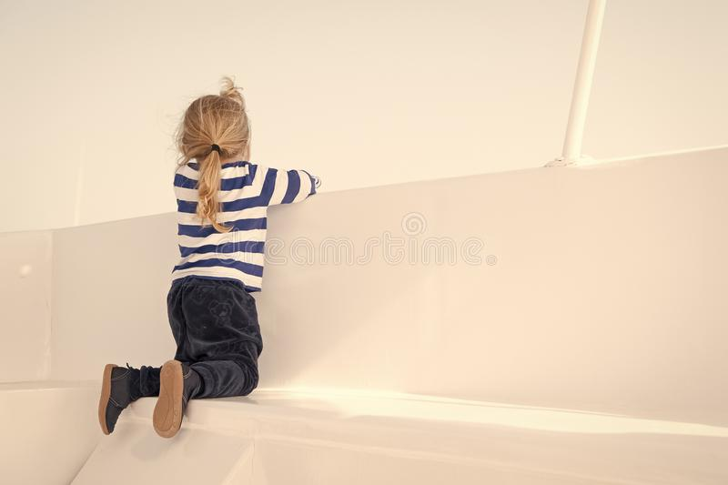 Small boy look from ship board, back view. Child on seat of boat on sunny blue sky. Kid with blond hair in navy clothes. Kids fashion and style. Summer royalty free stock photos