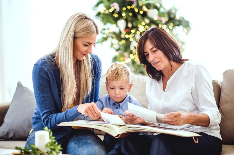 A small boy with mother and grandmother looking at photos at home at Christmas time. stock photos