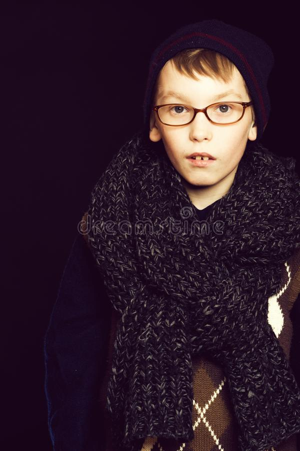 Small boy nerd in glasses. Small boy or cute nerd kid in glasses, hat and fashionable knitted scarf on black background royalty free stock image
