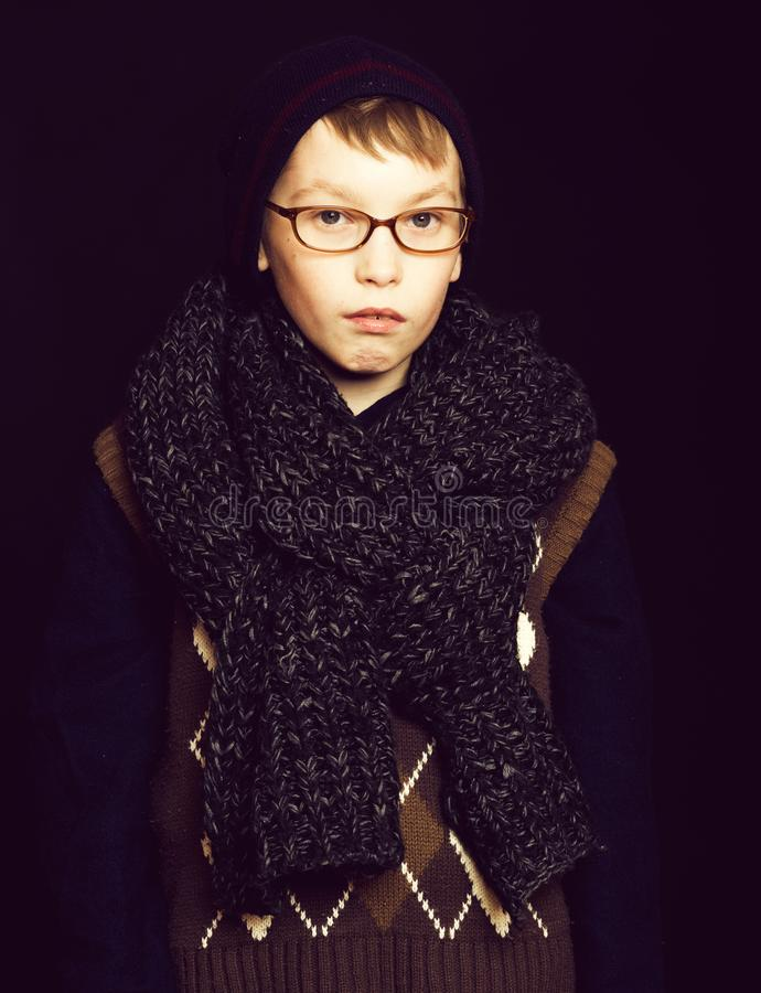 Small boy nerd in glasses. Small boy or cute nerd kid in glasses, hat and fashionable knitted scarf on black background royalty free stock photography