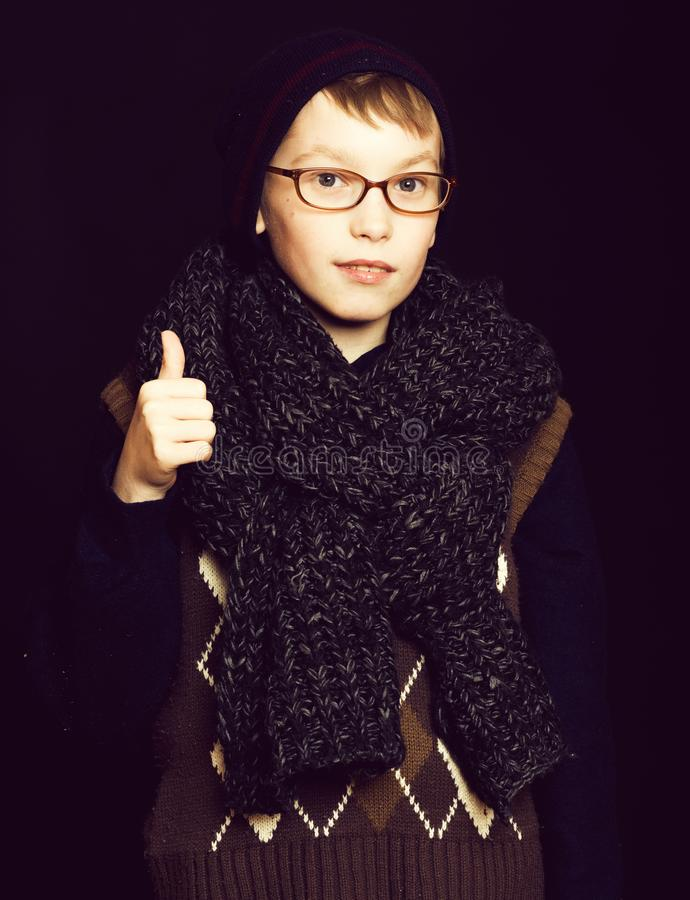 Small boy nerd in glasses. Small smiling boy or cute nerd kid in glasses, hat and fashionable knitted scarf on black background, holds thumb up royalty free stock image