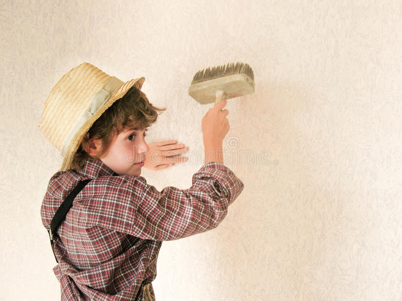 Small boy paints the wall. Child labour concept. Tired boy painter is very tired after work. Tired schoolchild in shirt sleeping o stock photo